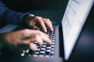 An employee works on the company laptop not aware of the latest cybercrime.